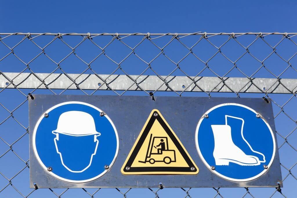 Sicherheitsschilder für Arbeitssicherheit an einem Zaun