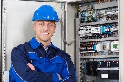 Männliche Elektrofachkraft vor Schaltschrank.