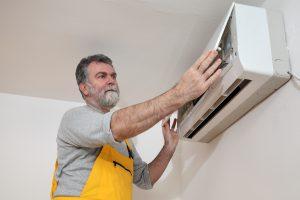 Elektrofachkraft für festgelegte Tätigkeiten installiert eine Klimaanlage in einem Raum