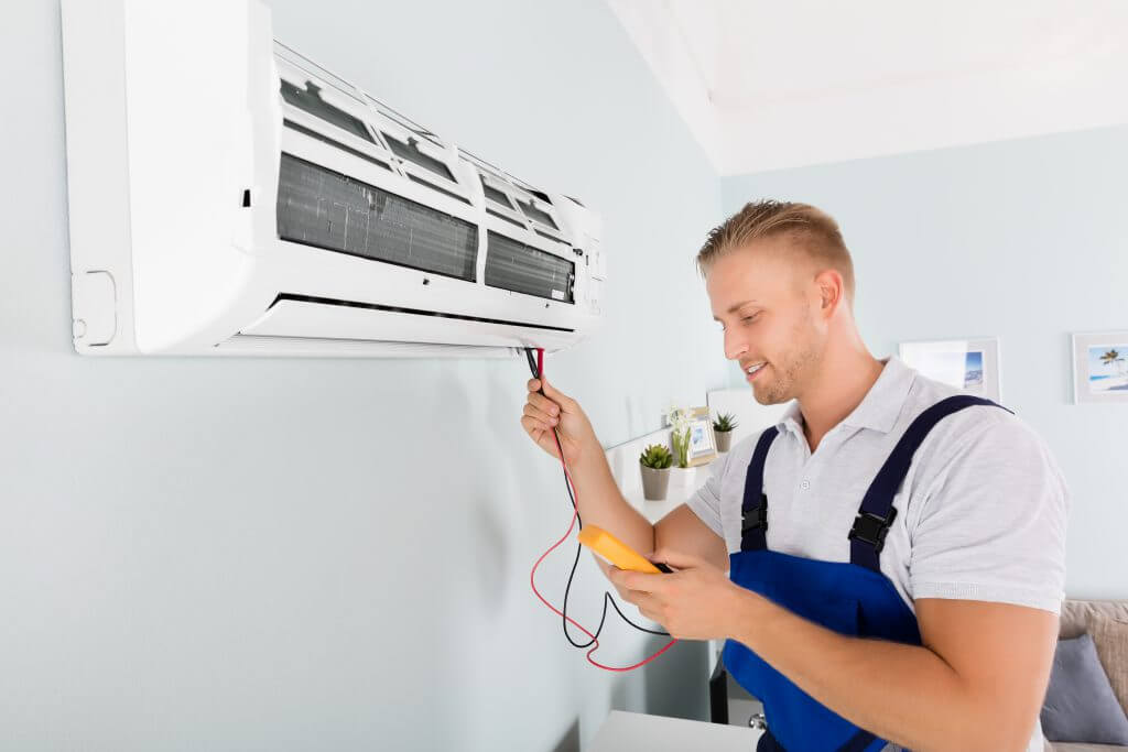 Männliche elektrotechnisch unterwiesene Person, prüft Klimaanlage Mit Digitalem Multimeter.