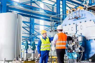 Arbeiter und Manager in einer industriellen Fabrik reden über die Gefährdungsbeurteilung einer Maschine, zum systematischen Arbeitsschutz.