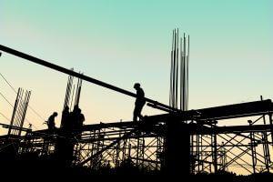 Silhouette von Bauarbeitern mit persönlicher Schutzausruestung gegen Absturz, die auf einem hohen Gerüst arbeiten. Konzept Sicherheit am Arbeitsplatz.
