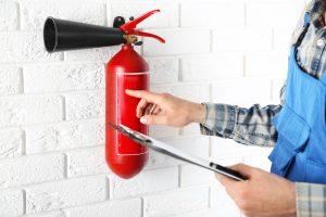 Ein Brandschutzbeauftragter zeigt mit dem rechten Zeigefinger auf einen Feuerlöscher und hält in der linken hand ein Clipboard