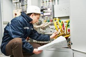 Die verantwortliche Elektrofachkraft, während der Inspektion einer Hochspannungs-Stromleitung, in einem industriellen Verteilerschrank.