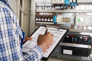 Prüfung ortsfester elektrischer Anlagen: Der Elektriker steht vor einem Schaltschrank und notiert die Ergebnisse der Prüfung auf einem schwarzen Clipboard.