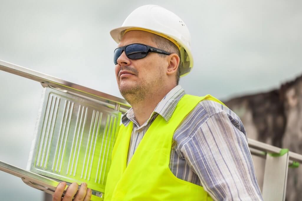 Arbeitssicherheit: Befähigte Person mit Leiter in der Hand